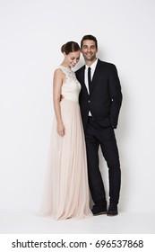 Glamorous couple in formal wear, smiling in studio