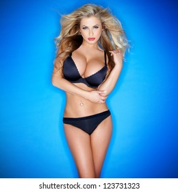 Glamorous curvy blonde woman with a sexy body and large breasts posing in black lingerie on a blue studio background with vignetting