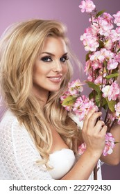 15241be929 Glamorous curvy blonde woman with a sexy body posing with flowers on a pink  studio background