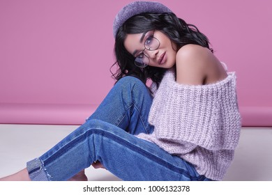 Glamorous fashion portrait of beautiful charming asian girl in purple sweater on bright pink background in studio
