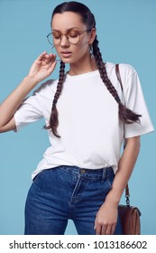 Glamorous fashion portrait of beautiful charming hispanic girl in white t-shirt, jeans and glasses on bright background in the studio