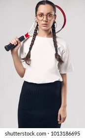 Glamorous fashion portrait of beautiful charming hispanic girl in white t-shirt and glasses with tennis racquet on bright background in the studio