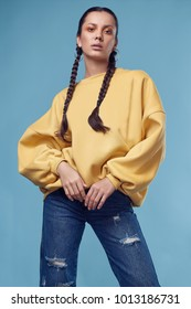 Glamorous fashion portrait of beautiful charming hispanic girl in jeans and yellow hoody on blue background in the studio