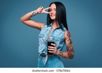 Glamorous fashion portrait of beautiful charming girl with tattoo holding a soda on a bright background in the studio