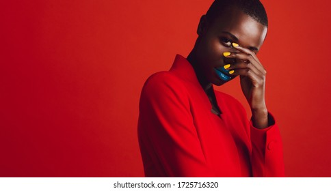 Glamorous female model on red background. African woman with buzz cut hairstyle and vibrant makeup looking at camera.