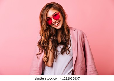 Glamorous ginger girl in pink glasses expressing positive emotions. Happy attractive young woman enjoying photoshoot.