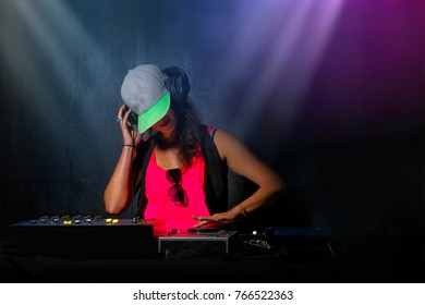 Glamorous girl deejay at work mixing sound on her console at a party or night club with colorful strobe lights background.