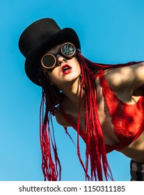 Glamorous girl with scarlet dreadlocks, a red swimsuit, black hat and welding glasses poses on the blue sky background. Free space for your text