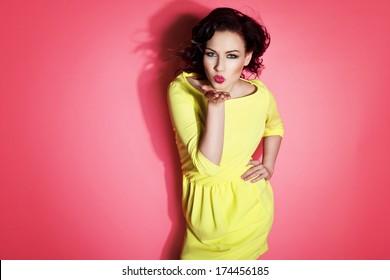 Glamorous girl wearing yellow dress, sending a kiss