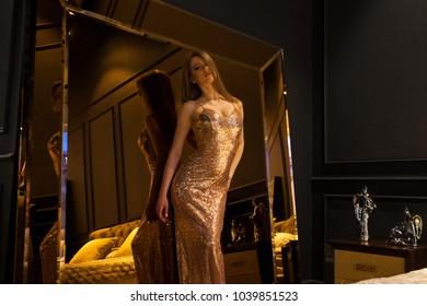 Glamorous interior golden big mirror. Fashion Beautiful young woman in sexy dress