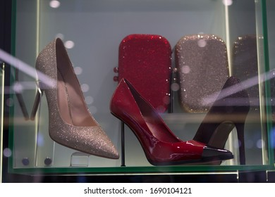 glamorous, luxurious, shiny and red high-heeled shoes, clutch bags on a shop window
