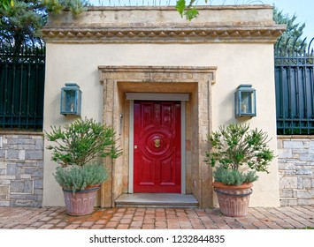 glamorous  luxury house entrance red door and flowerpots