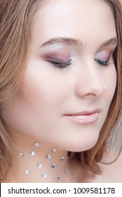 Glamorous makeup for the eyes closed blonde with pure skin and rhinestones on the neck close-up