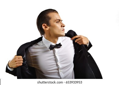 Glamorous male model in white shirt, black jacket, and bow-tie - putting on the jacket.
