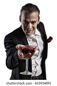 Glamorous male model in white shirt, black jacket, and vampire make-up offering a glass of blood in a martini glass.