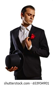 Glamorous male model in white shirt, black jacket and black hat in his hand.
