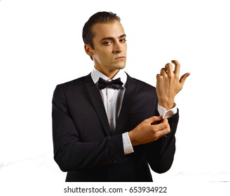 Glamorous male model in white shirt, black jacket, and bow-tie - buttoning his shirt sleeve.