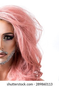 Glamorous man dressed as a woman in heavy mascara, pink hair and lipstick with a silver glitter beard isolated on white.