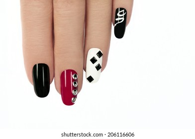 Glamorous manicure with different colors of paint and rhinestones square and round shapes on a white background.