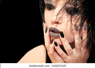 Glamorous matte black gray makeup, and manicures on a sharply oval-shaped nails with feathers of a model on a background.