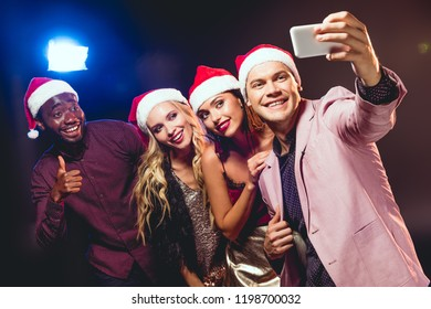 glamorous multicultural friends in santa hats taking selfie on smartphone