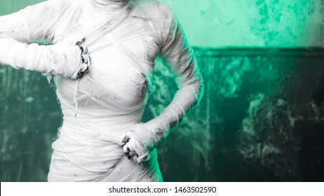 Glamorous mummy. Portrait of a young beautiful woman in bandages all over her body. Halloween or plastic surgery concept, Green light, mummy breaks into the bandages themselves