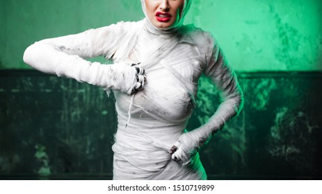 Glamorous mummy. Portrait of a young beautiful woman in bandages Tears her bandages. Halloween or plastic surgery concept, Green light