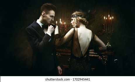 Glamorous passionate couple of a man and a woman in the style of 1920s. Fashion clothes, make-up and hair in luxurious retro style.