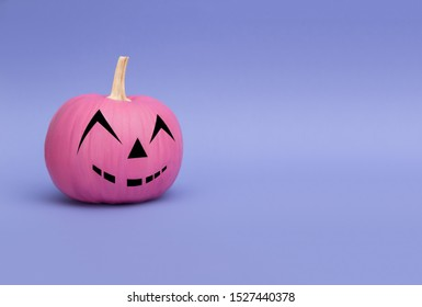 Glamorous pink pumpkin for Halloween, which smiles on a purple background.