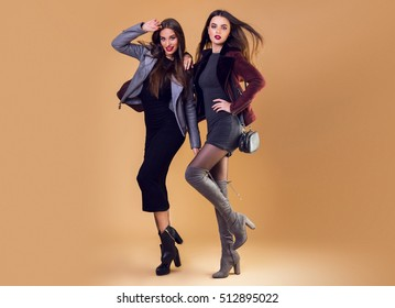 Glamorous  pretty two girls posing over beige   background ,  wearing casual winter jacket and dress. high heels.  Windy hairstyle. Full length image.