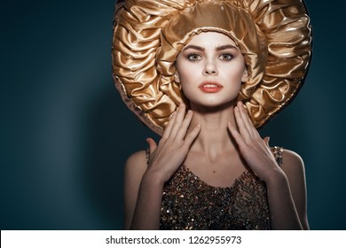 Glamorous pretty woman in a big gold-colored hat and dress