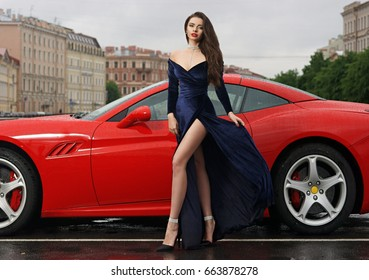 Glamorous sexy fashionable woman with long legs in blue evening dress and long brown hair standing against red sport car at city street on overcast day