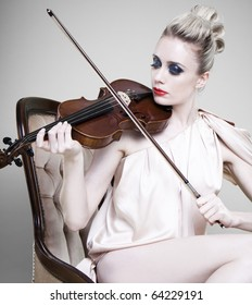 Glamorous sexy young woman playing violin, light studio background.