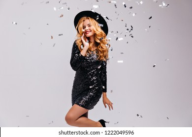 Glamorous smiling girl in black hat posing on light background. Indoor shot of stunning curly blonde woman in shiny dress.