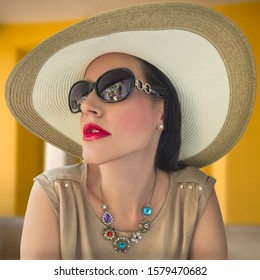 A glamorous socialite wearing a large rim straw hat and big sunglasses looks up in the Plaza. The red color full lips accentuate the colorful ruby necklace.