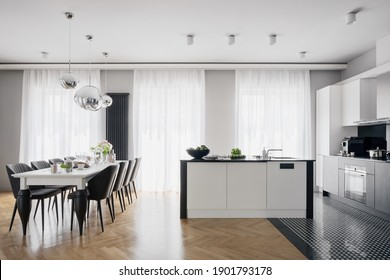 Glamorous and spacious kitchen with black and white furniture, many big windows and with stylish dining table for eight