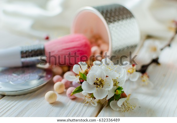 Glamorous spring still life. Powder for the face in balls on a light wooden table