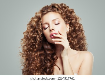 Glamorous woman fashion model portrait. Beautiful girl with long curly hair