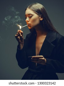 glamorous woman lights a cigar.She brings flame of burning match to a cigar. Atmosphere of retro in studio