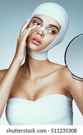 Glamorous woman in medical bandages touching her new nose. Beauty victim after plastic operation. Plastic Surgery concept.
