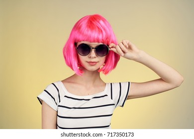 glamorous woman in a striped T-shirt in sunglasses on a yellow background portrait