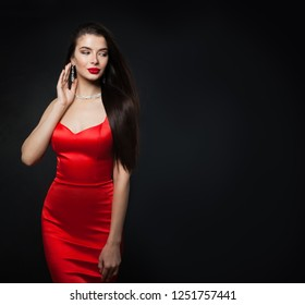 Glamorous woman wearing red dress. Sexy model with red lips makeup and diamond jewelry on black background with copy space