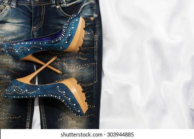 Glamorous women's fashion, jeans, shoes in rhinestones, lying on white silk