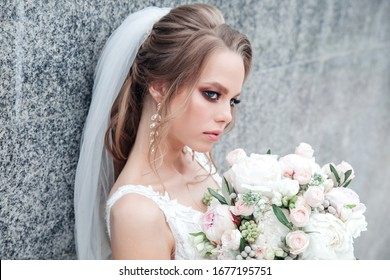 Glamorous young bride with bouquet in wedding dress outdoor
