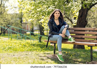 Glamorous young Caucasian woman in black leather jacket sitting in the park on the bench