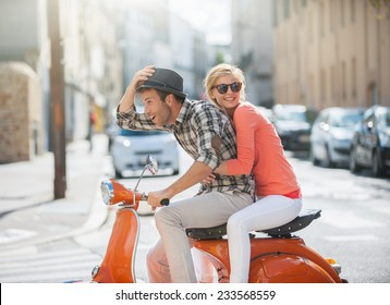 glamorous  young couple riding  a vintage scooter in the street, man wears a hat and woman has a topknot and sunglasses