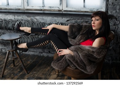 Glamorous young lady in fur coat posing by the window in a vintage interior, studio shot