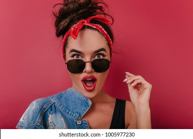 Glamorous young woman with big dark eyes posing with mouth open. European female model with red ribbon standing on claret background and looking through glasses.