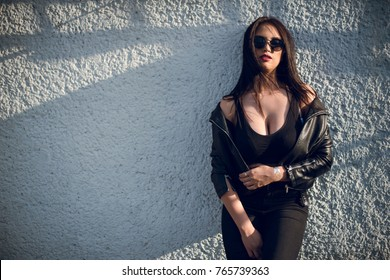 Glamorous young woman in black leather jacket, jeans and sunglasses on the rooftop