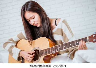 Glamorous young woman with her guitar on the bed